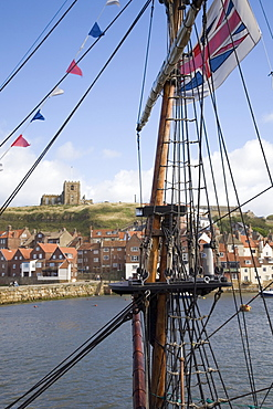 Old Port and St. Mary's church on East Cliff across River Esk, through rigging of replica of Captain Cook's ship Bark Endeavour, Whitby, Heritage Coast of North East England, North Yorkshire, England, United Kingdom, Europe