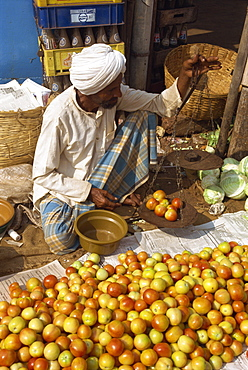 Man weighing tomatoes on scales, Mapusa Market, Goa, India, Asia