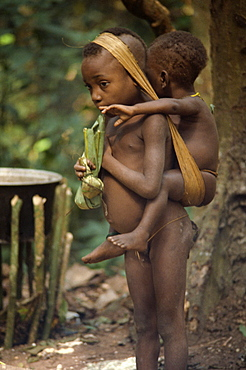 Pygmy girl carrying a young boy, Central African Republic, Africa