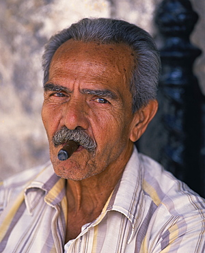 Head and shoulders portrait of an eldery man with moustache smoking a cigar, looking at the camera, Habana (Havana), Cuba, West Indies, Caribbean, Central America