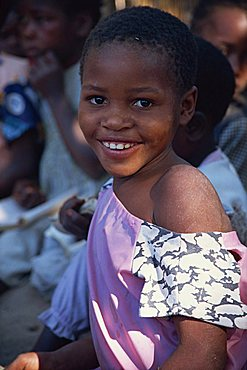 Head and shoulders portrait of girl, smiling and looking at the camera, Mozambique, Africa