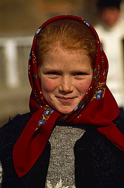 Head and shoulders portrait of a young Romanian girl with red hair wearing a red head scarf, smiling and looking at the camera, in Bottiza village, Romania, Europe