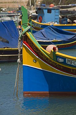 Brightly coloured fishing boats called Luzzus with the eye of Osiris to ward off evil at Marsaxlokk, a fishing village, Malta, Mediterranean, Europe