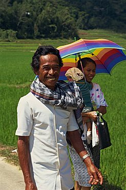 Portrait of a family, mother, father and baby, walking through a rice field, the man smiling and looking at the camera, Toraja area, Sulawesi, Indonesia, Southeast Asia, Asia