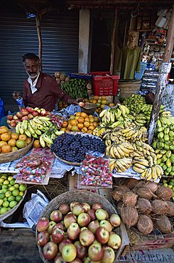 Elderly man at his fruit stall in Munnar a small town in the tea country high in the Western Ghats, Kerala, India, Asia