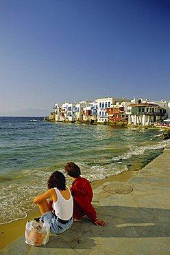 Couple looking towards Little Venice in the Alefkandra district of Mykonos Town, Mykonos, Cyclades Islands, Greece, Europe