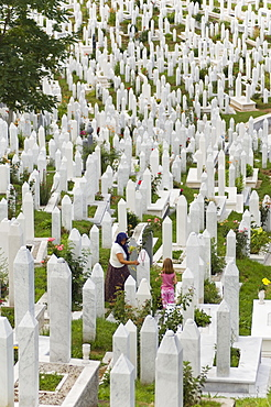 Muslim woman and child tend a grave at a war cemetery, Sarajevo, Bosnia, Bosnia-Herzegovina, Europe