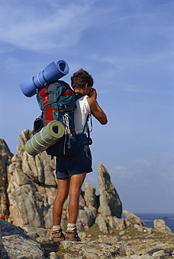 Portrait of the back view of a backpacker with bedding rolls and rucksack on Ouessant island in Brittany, France, Europe
