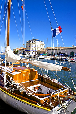 Tourist boats in marina, and French flag, in Marseillan harbor, Herault, Languedoc-Roussillon region, France, Europe