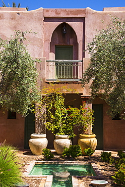Typical Moroccan architecture, riad adobe walls, fountain and flower pots, Morocco, North Africa, Africa