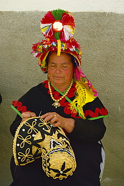 Portrait of a Spanish woman in traditional dress decorating a straw hat, in Extremadura, Spain, Europe