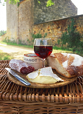 Still life of bread, glass of red wine, cheese and sausage, picnic meal on top of a wicker basket, in the Dordogne, France, Europe - 681-2176