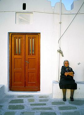 Old lady sitting by church, Mykonos (Mikonos), Cyclades Islands, Greek Islands, Greece, Europe