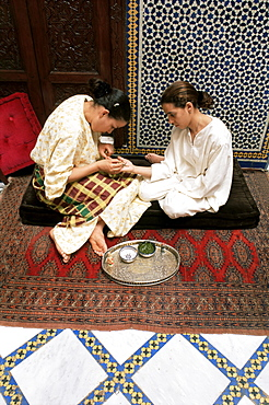 Applying a design to a young woman's hand, Fez, Morocco, North Africa, Africa