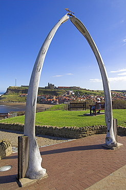 Whalebone arch on Seafront, with Whitby abbey ruin in distance, Whitby, North Yorkshire, Yorkshire, England, United Kingdom, Europe