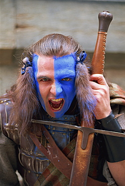 """Head and shoulders portrait of """"Braveheart"""", Highlander man in leather costume with facial paint of blue and white, snarling at the camera, Edinburgh, Lothian, Scotland, United Kingdom, Europe"""