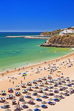 Holidaymakers sunbathing under beach umbrellas on the sandy beach at Praia do Tunel, Albufeira Beach, Algarve, Portugal, Europe