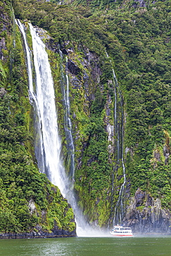 Stirling Falls waterfall and tourist boat, Fiordland National Park, UNESCO World Heritage Site, Milford Sound, New Zealand, Pacific
