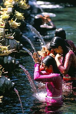 Young women at Tirta Empul temple, Ubud region, island of Bali, Indonesia, Southeast Asia, Asia