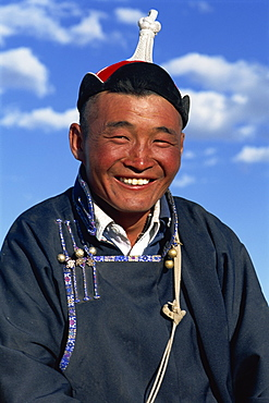 Head and shoulders portrait of a smiling nomad man in traditional clothing, looking at the camera, at Naadam Festival, Altai, Gov-altai, Mongolia, Central Asia, Asia
