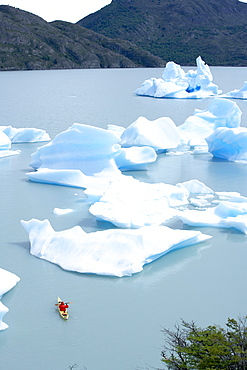 Person kayaking between floating icebergs, Lago Gray (Lake Gray), Torres del Paine National Park, Patagonian Andes, Patagonia, Chile, South America