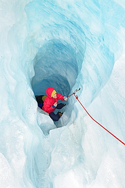 Rock climber moving up ice cave, Fox Glacier, South Island, New Zealand, Pacific