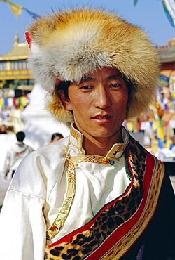 Young Tibetan man wearing typical hat and dress during Losar (Tibetan New Year) at Bodhnath, Katmandu, Nepal