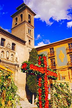 Dia de la Cruz, floral cross with Santa Ana church in the background, Plaza Nova, Granada, Andalucia, Spain