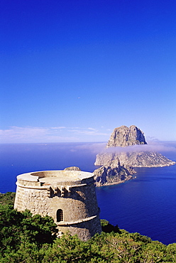 View of a defence tower and rocky islet of Es Vedra, surrounded by mist, near Sant Antoni, Ibiza, Balearic Islands, Spain, Mediterranean, Europe