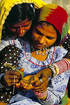 Two young women applying henna to the hand, Pushkar, Rajasthan state, India, Asia