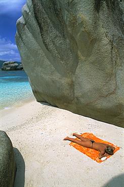 Woman sunbathing on beach beween rocks, Coco Island, Praslin, Seychelles, Indian Ocean, Africa