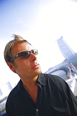 Portrait of a man outdoors wearing sunglasses and a casual black shirt