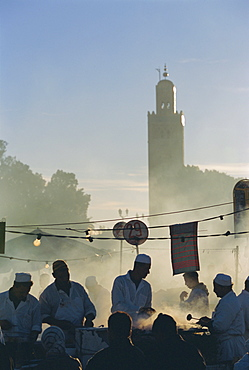 Chefs preparing food at stalls in the Djemma-el-Fna square, with the Koutoubia minaret behind, Marrakech, Morocco