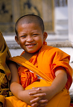 Portrait of a young Buddhist monk (novice), smiling and looking at the camera, Bangkok, Thailand, Southeast Asia, Asia