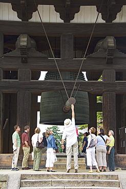 Tourists look at big cast iron bell, Todaiji (Big Buddha) Temple, constructed in the 8th century Nara City, Nara Prefecture, Honshu Island, Japan, Asia