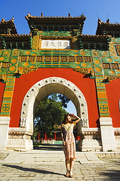 Chinese girl under a glazed archway at the Confucius Temple Imperial College, built in 1306 by the grandson of Kublai Khan, administering the official Confucian examination system, Beijing, China, Asia