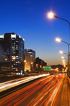 Car light trails and modern architecture on a city ring road, Beijing, China, Asia