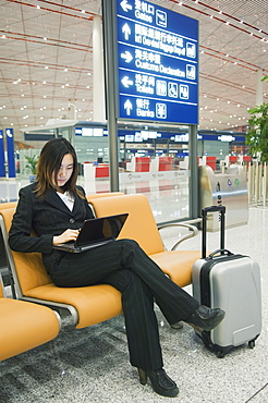 A Chinese business woman using a laptop computer at Beijing Capital Airport, part of new Terminal 3 building opened February 2008, second largest building in the world, Beijing, China, Asia