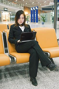 A Chinese business woman using a laptop computer at Beijing Capital Airport part of new Terminal 3 building opened February 2008, second largest building in the world, Beijing China, Asia