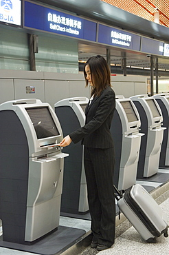 A Chinese business woman using the self service check in machines at Beijing Capital Airport part of new Terminal 3 building opened February 2008, second largest building in the world, Beijing, China, Asia