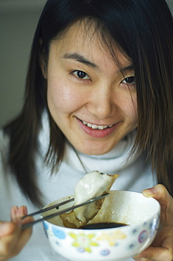 A Chinese girl eating dumplings, which are eaten traditionally on the Eve of Chinese New Year, China, Asia