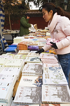 A Chinese girl looking for books at Ditan Park book fair, Beijing, China, Asia