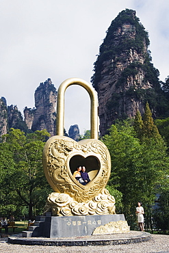 A couple in a giant love heart lock, Zhangjiajie Forest Park, Wulingyuan Scenic Area, UNESCO World Heritage Site, Hunan Province, China, Asia