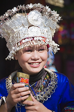 Girl in traditional clothing welcoming visitors with a horn of rice wine at a Miao New Year festival in Xijiang, Guizhou Province, China, Asia