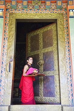 Young monk at a temple doorway, Khamsum Yuelley Namgyal Chorten built in 1999, Punakha, Bhutan, Asia