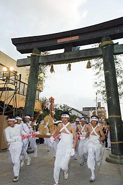 Rice bales being carried through a torii gate at Hadaka Matsuri (Naked Festival), Hofu city, Yamaguchi Prefecture, Japan, Asia