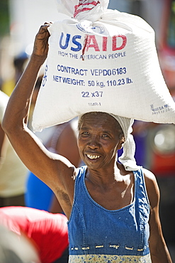 A woman carrying rice, USAid food distribution after the January 2010 earthquake, Port au Prince, Haiti, West Indies, Caribbean, Central America