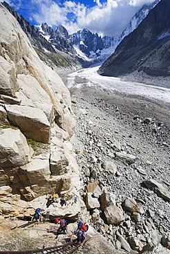 Climbers on a ladder on a rock face above Mer de Glace, Mont Blanc range, Chamonix, French Alps, France, Europe
