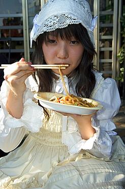 Tokyo subculture, teenage girl eating noodles, Harajuku, Yoyogi koen park, Tokyo, Honshu, Japan, Asia