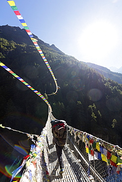 Porter crossing a suspension bridge decorated in Tibetan prayer flags, Sagarmatha National Park, UNESCO World Heritage Site, Khumbu Valley, Nepal, Asia